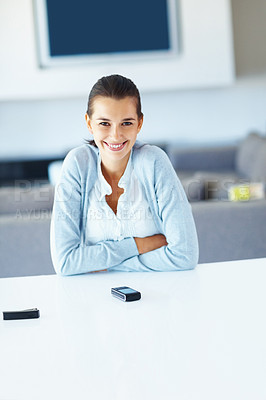 Buy stock photo Portrait of young woman with cell phone on desk and smiling