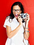 Happy young woman winking with a camera in hand