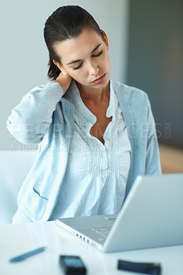 Buy stock photo Young woman suffering from neck pain while working on laptop
