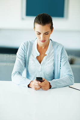 Buy stock photo Portrait of young woman sending text message from cellphone