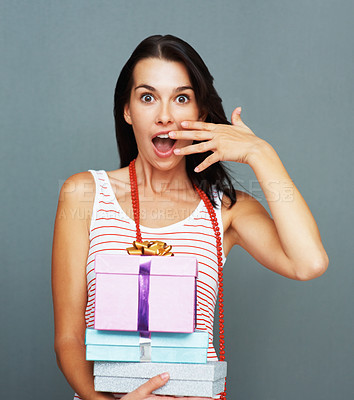 Buy stock photo Portrait of surprised young woman holding a stack of gifts on a grey background