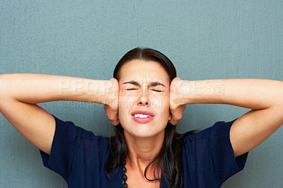 Buy stock photo Closeup of frustrated young woman holding her ears against wall