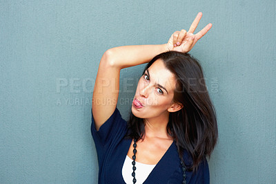 Buy stock photo Young woman making funny face while showing victory sign
