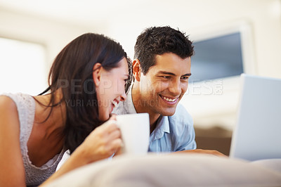 Buy stock photo Cheerful young woman with coffee cup lying beside man working on laptop