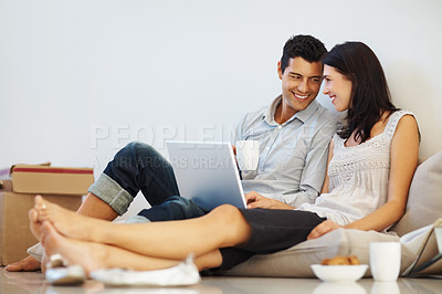 Buy stock photo Happy young couple using laptop while sitting on the floor