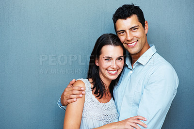 Buy stock photo Portrait of smiling couple embracing on blue background