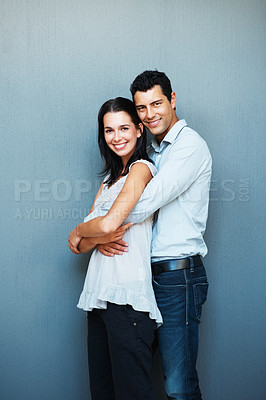 Buy stock photo Portrait of smiling young man embracing his girlfriend from behind