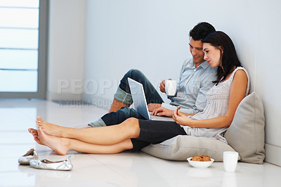 Buy stock photo Relaxed young couple using laptop at home