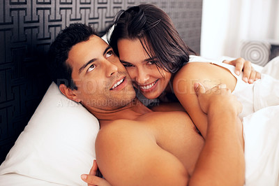 Buy stock photo Portrait of young couple cuddling while lying on bed