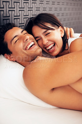 Buy stock photo Playful young couple embracing while lying in bed