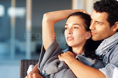 Buy stock photo Dreaming young couple sitting in the living room and looking away