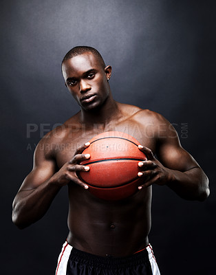 Buy stock photo Portrait of an athetic young African American man holding a basketball tightly against a dark background