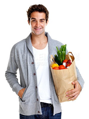 Buy stock photo Portrait of smiling young man holding shopping bag full of groceries isolated against white