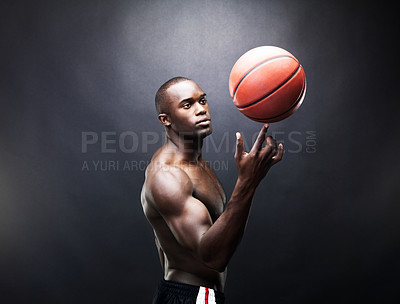 Buy stock photo Portrait of a muscular African American guy spinning a basketball expertly on his finger on a dark background