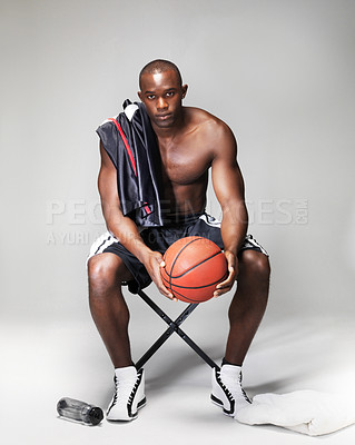 Buy stock photo Portrait of a healthy young basketball player resting after a game against grey background