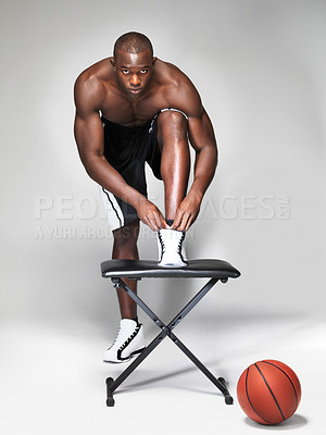 Buy stock photo Portrait of a young basketball player male ties his shoes laces against white background