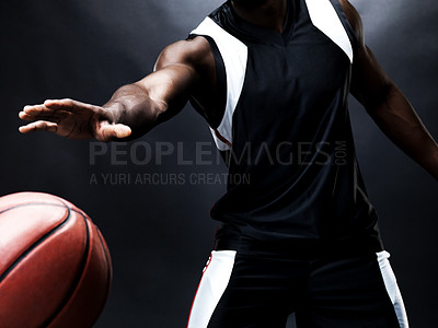 Buy stock photo Cropped low-angle image of a young basketball player bouncing the ball, with a dark background
