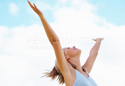Buy stock photo Smiling woman with arms raised towards the sky on sunny day