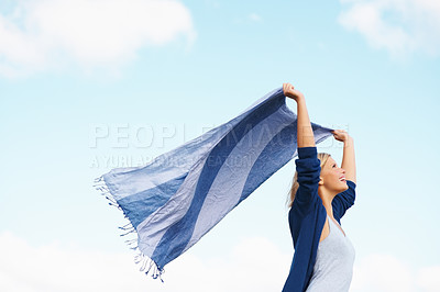 Buy stock photo Happy woman holding scarf against blue sky