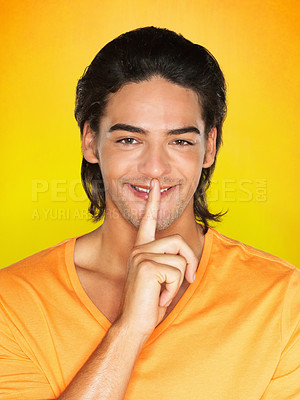 Buy stock photo Attractive man giving silence gesture against yellow background