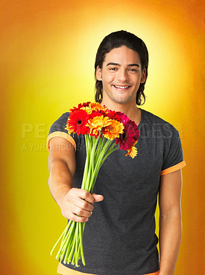 Buy stock photo Attractive man holding out a bouquet of flowers for you, against a golden background