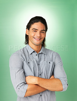 Buy stock photo Smiling man standing with arms crossed against green background