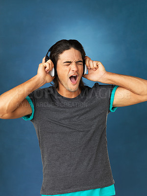 Buy stock photo Man singing while listening to headphones against blue background