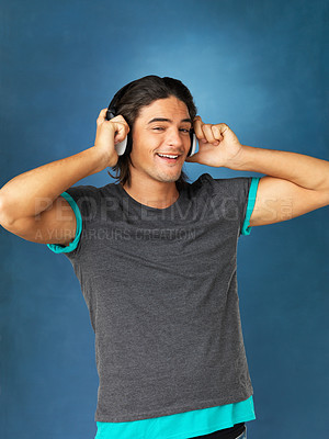 Buy stock photo Handsome man smiling while listening to headphones