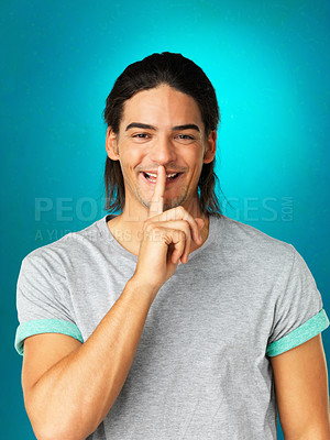 Buy stock photo Attractive man laughing while making silence gesture