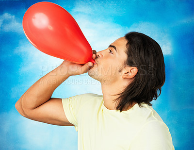 Buy stock photo Side view of young man blowing up red balloon