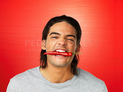 Buy stock photo Young man holding red hot chili pepper with teeth on red background