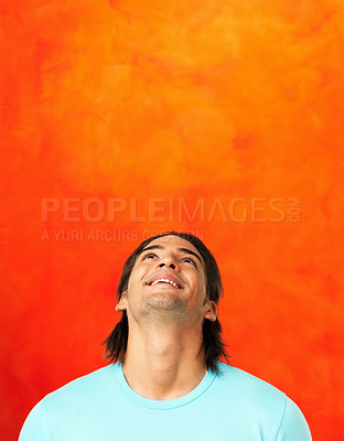 Buy stock photo Handsome man looking up and smiling against orange background