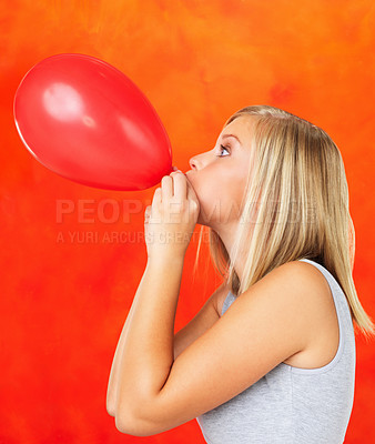 Buy stock photo Side view of pretty woman blowing up red balloon