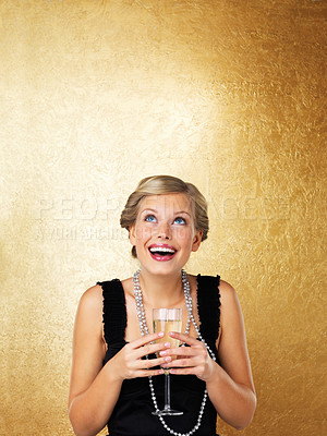 Buy stock photo Happy woman holding champagne flute and looking up