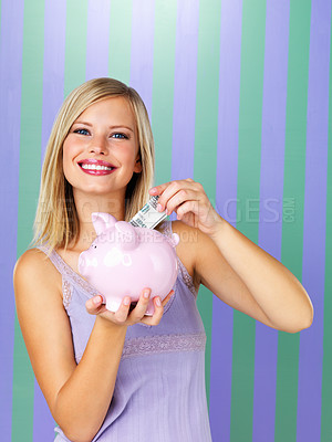 Buy stock photo Pretty woman saving money in piggy bank