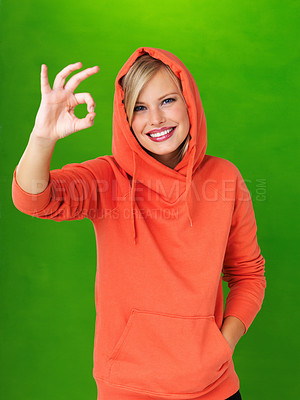 Buy stock photo Pretty woman with hooded sweatshirt giving ok sign on green background