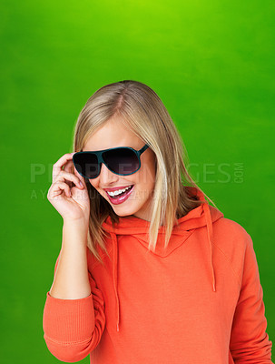 Buy stock photo Pretty woman adjusting her sunglasses on green background