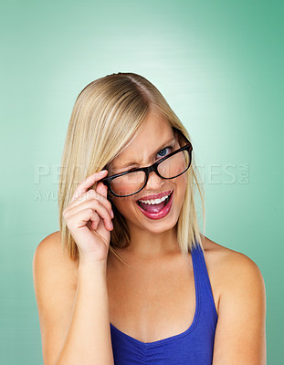 Buy stock photo Woman holding glasses and winking on green background