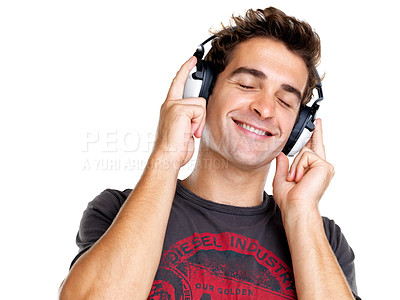 Buy stock photo Portrait of a cool young guy listening to music on headphone against white background