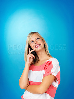 Buy stock photo Woman smiling while on cell phone against blue background