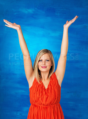 Buy stock photo Pretty woman in red extending arms overhead