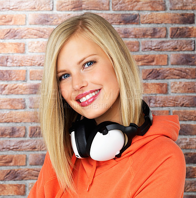 Buy stock photo Closeup of pretty blonde woman in an orange hoodie with headphones around her neck against a brick background