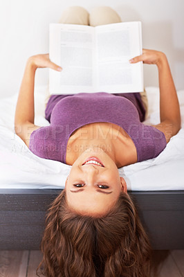 Buy stock photo Happy girl lying upside down in bed with head over the edge and holding a book