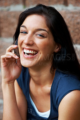 Buy stock photo Portrait of a happy young lady enjoying conversation on cellphone against brick wall