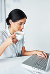 Busy young business woman drinking coffee and using laptop