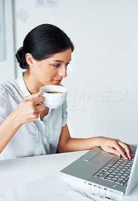 Buy stock photo Portrait of a smart young business woman having a cup of coffee while using laptop in the office