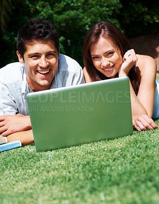 Buy stock photo Portrait of a beautiful young couple lying on the ground with the laptop in the garden