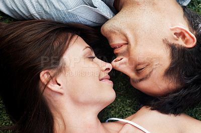 Buy stock photo Closeup portrait of an affectionate young couple lying face to face on grass - Outdoor