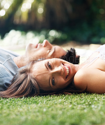 Buy stock photo Portrait of a pretty young woman lying on grass with her boyfriend in the park - copyspace