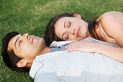 Buy stock photo Portrait of a cute young couple relaxing on grass - Outdoor